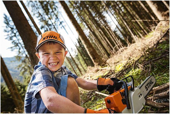 мальчик в лесу с игрушечной пилой штиль